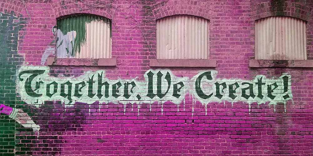 "Brick wall with ""together we create"""
